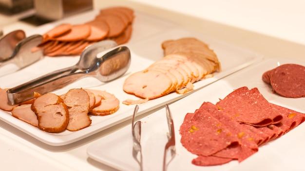 Buffet libre en el hotel. variedad de jamón y chorizo en platos blancos con pinzas.