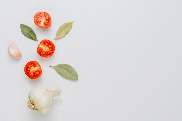 Un bulbo y un diente de ajo entero orgánico con las hojas de laurel y los tomates de cereza partidos en dos en el fondo blanco
