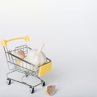 Bulbos del ajo en carro de compras en el contexto blanco