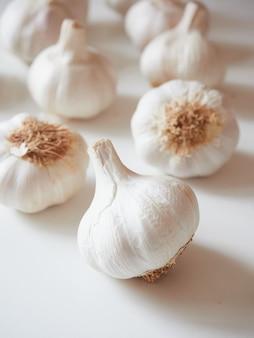Bulbos de ajo enteros sobre mesa blanca