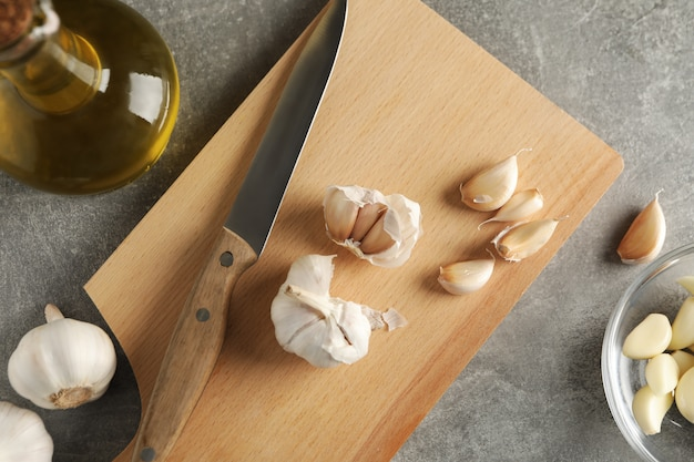 Bulbos de ajo, rodajas, aceite, cuchillo, tablero sobre fondo de madera gris. vista superior