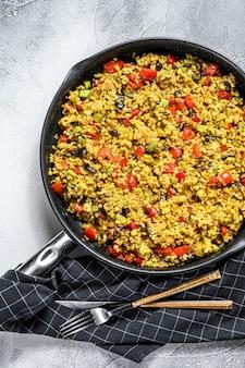 Bulgur cocido con verduras en una sartén. fondo gris