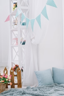 Bunting sobre la cama con canasta de tulipanes; cerca; manta de piel y cojin en casa