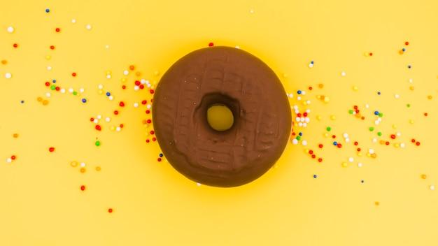 Buñuelo de chocolate con colorido asperja sobre fondo amarillo