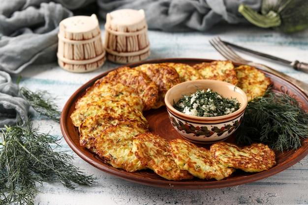 Buñuelos de calabacín se colocan en un plato, en el centro hay salsa de crema agria con ajo y eneldo