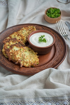 Buñuelos de calabacín. crepes de calabacín vegetarianos servidos con hierbas frescas y crema agria
