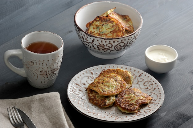 Buñuelos de calabacín con eneldo en un plato hondo, té, crema agria