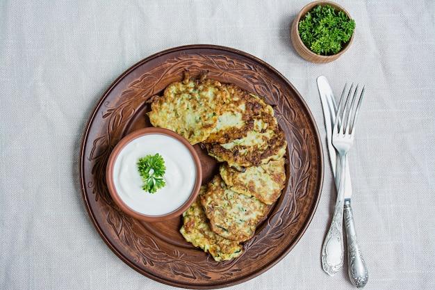 Buñuelos de calabacín, panqueques vegetarianos de calabacín, servidos con hierbas frescas y crema agria