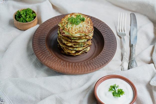Buñuelos de calabacín servido con hierbas frescas y crema agria, vista desde arriba.