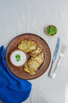 Buñuelos de calabacín, tortitas de calabacín vegetarianas, servidas con hierbas frescas y crema agria.