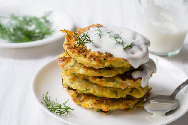 Buñuelos de calabacín, zanahoria, parmesano en plato con eneldo y yogurt