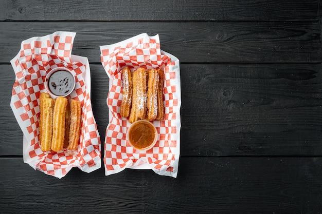Buñuelos fritos en marrón, bolsa para llevar en bandeja de papel, sobre fondo de mesa de madera negra, vista superior plana con espacio para texto, copyspace
