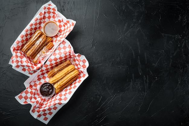 Buñuelos fritos en marrón, bolsa para llevar en bandeja de papel, sobre fondo negro, vista superior plana con espacio para texto, copyspace