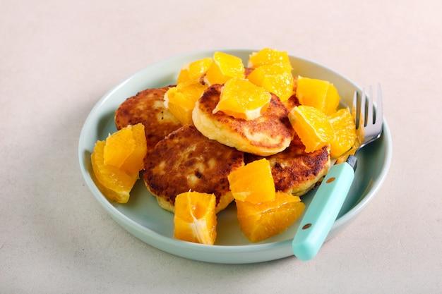 Buñuelos de requesón con naranjas en placa
