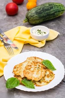 Buñuelos de vegetales fritos de calabacín y hojas de albahaca en un plato sobre la mesa