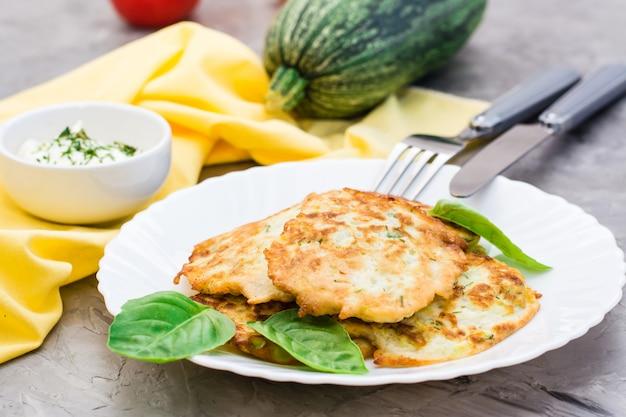Buñuelos de verduras fritas de calabacín y hojas de albahaca en un plato y cubiertos en la mesa