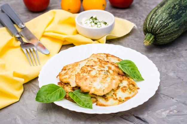 Buñuelos de verduras fritas de calabacín y hojas de albahaca en un plato y salsa de crema agria con verduras en un recipiente sobre la mesa