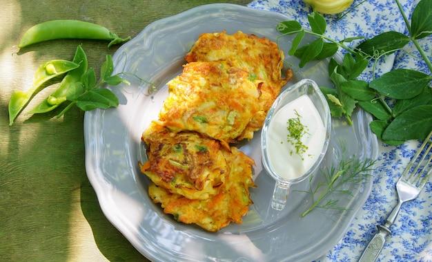 Buñuelos de zanahoria, calabacín y guisantes verdes con yogur griego