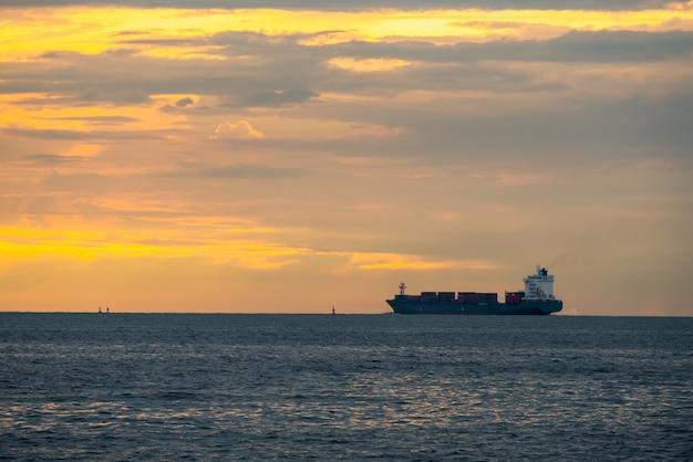 Buque de carga de contenedores de importación y exportación de logística en el puerto marítimo en el cielo del atardecer, transporte de carga por barco de contenedores