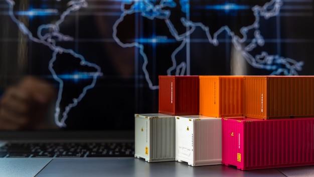 Buque de carga de contenedores de negocios globales en logística comercial de importación y exportación, entrega de envío de la empresa y tecnología de logística comercial industrial, contenedor en computadora portátil, enfoque selectivo.