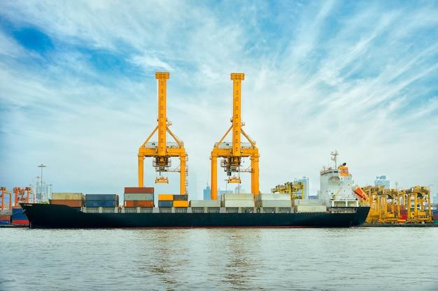 Buque de carga internacional de contenedores con puente de grúa trabajando en el fondo del astillero
