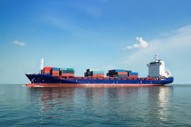 Buque de carga navega al mar para transportar carga en contenedores.