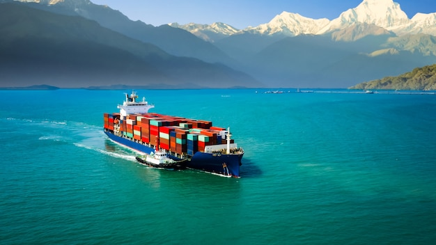 Buque portacontenedores navegando en el mar verde y arrastre de remolcador y montaña