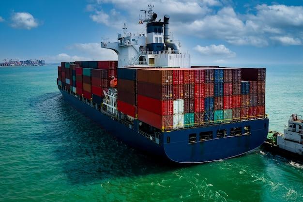 Buque portacontenedores navegando en el mar verde y arrastre de remolcadores y cielo azul