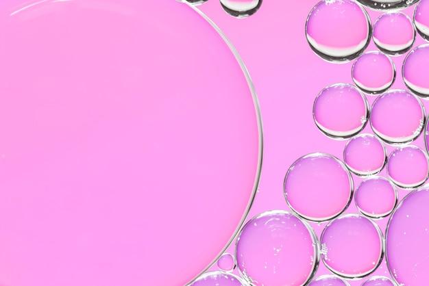 Burbujas de aire abstractas en líquido sobre fondo rosa