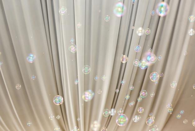 Burbujas en el banquete de boda interior contra las cortinas blancas.