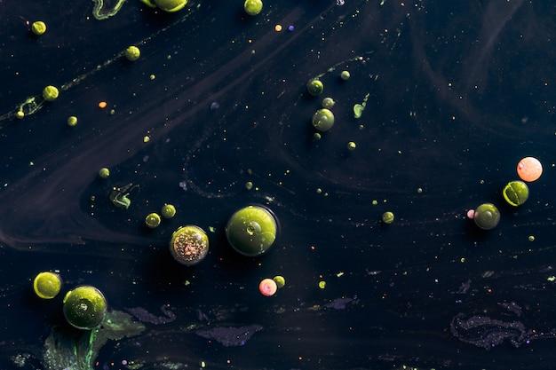 Burbujas verdes en la superficie del agua. toxinas en la superficie del líquido. foto abstracta macro.