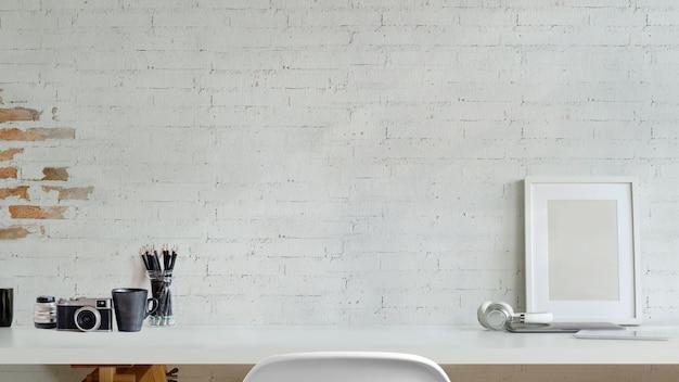 Se burlan de marco, cámara en el escritorio sobre la pared de ladrillo blanco. espacio de trabajo y espacio de copia