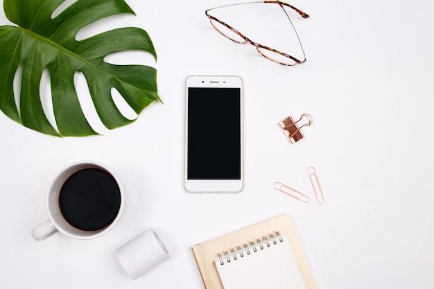 Burlarse del área de trabajo con el teléfono inteligente, hoja de palma tropical en el fondo blanco.