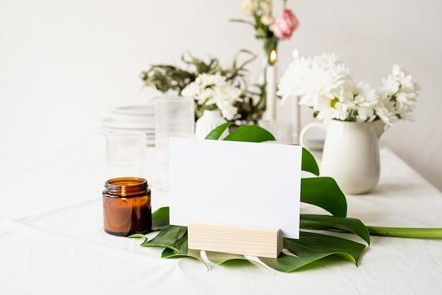 Burlarse de la etiqueta del marco del menú en blanco en el bar restaurante, soporte para folletos con papel blanco, tarjeta de carpa de madera en la hoja de monstera en la mesa del restaurante