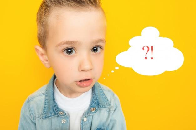 Burlarse de niño divertido perplejo sobre un fondo amarillo