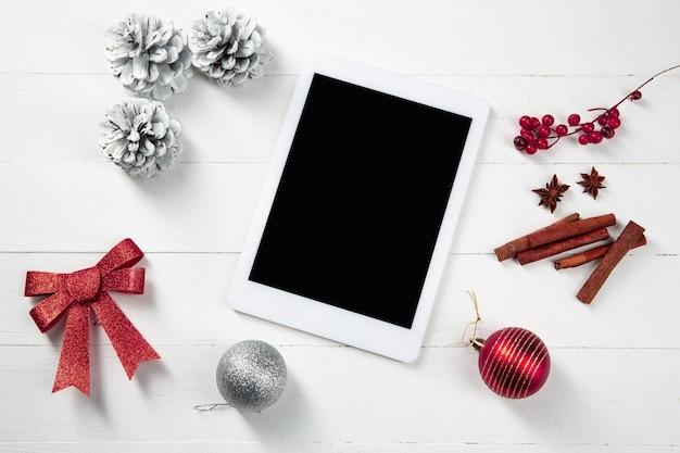Burlarse de la pantalla vacía en blanco de la tableta en la mesa de madera blanca