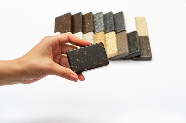 Burlarse de piedras naturales, vista superior, primer plano. manos femeninas anuncia materiales de reparación. pavimentos, gres, encimeras.