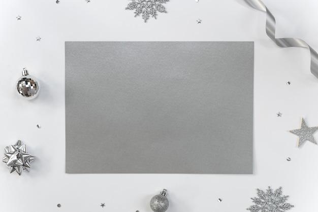 Burlarse de la tarjeta de felicitación de papel en blanco con adornos navideños y confeti.