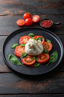Burrata, queso fresco italiano elaborado con nata y leche de búfala o vaca. en los tablones de la mesa de madera vieja de la placa negra.