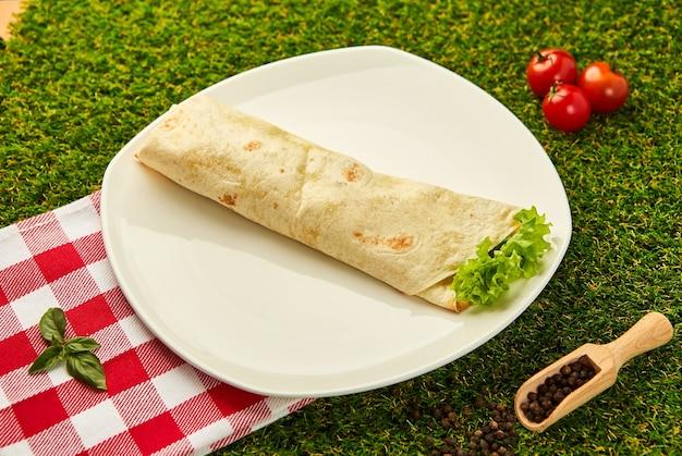 Burrito envuelve con pollo y verduras en un plato con pasto verde, shawarma mexicano