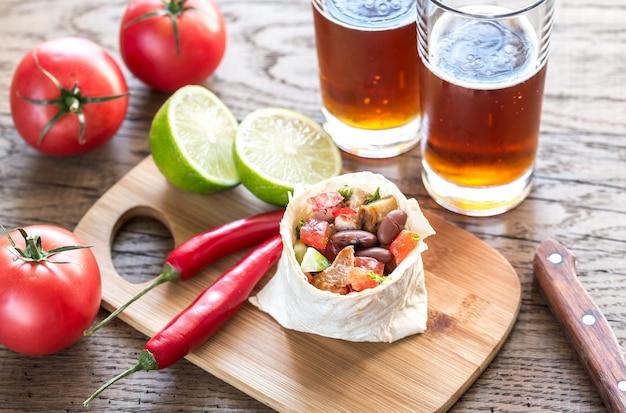 Burrito de pollo con vasos de cerveza