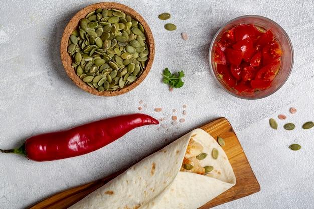 Burrito sobre tabla de madera cerca de pimientos, cardamomo y tomates en rodajas