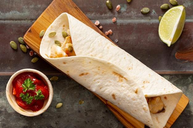 Burrito en tabla de cortar cerca de salsa de tomate, rodajas de lima y semillas de cardamomo