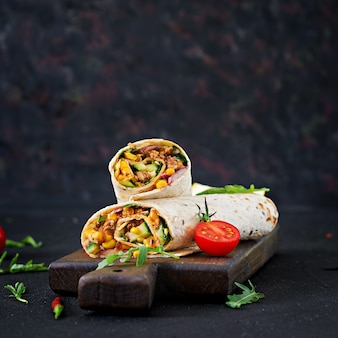 Burritos envuelve con carne y verduras sobre fondo negro. burrito de ternera, comida mexicana.