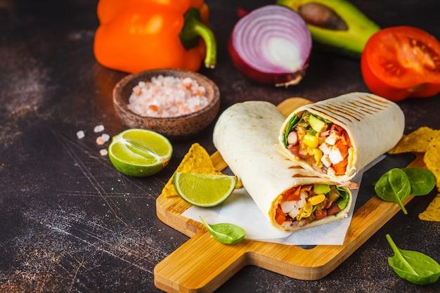 Burritos se envuelven con pollo, frijoles, maíz, tomates y aguacate sobre tabla de madera, fondo oscuro.
