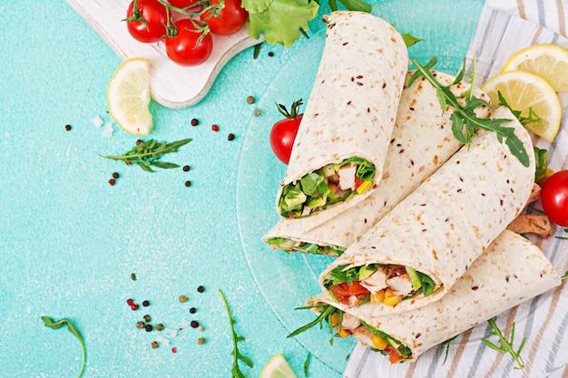 Burritos envuelven con pollo y verduras sobre fondo claro.