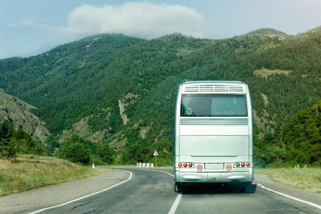 Bus turístico en la carretera entre las montañas verdes. vista trasera