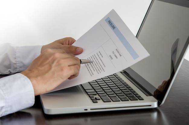 Buscador de trabajo revisar su currículum en su escritorio con lápiz y computadora portátil.