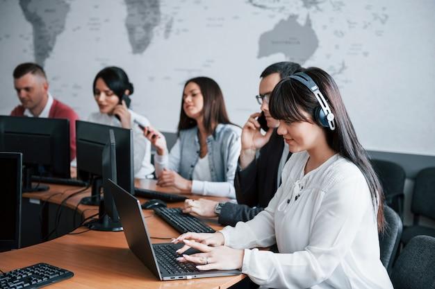 Buscando información. jóvenes que trabajan en el centro de llamadas. se acercan nuevas ofertas