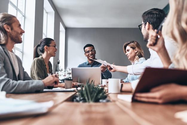 Buscando nuevas ideas juntos. grupo de jóvenes modernos en ropa casual elegante discutiendo negocios mientras trabaja en la oficina creativa